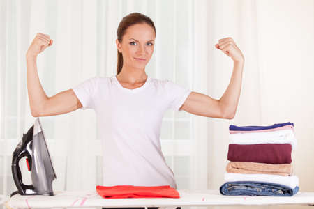 waist up: Portrait of smiling housewife ironing clothes. waist up housewife standing and showing muscles