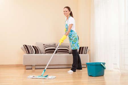 jonge vrouw doet het huishouden en schoonmaken. aantrekkelijk meisje dweilen vloer in de slaapkamer