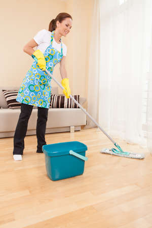 closeup of woman doing housework and cleaning. beautiful girl mopping floor in bedroom photo
