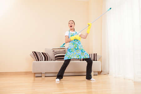 funny woman mopping floor and playing. beautiful girl playing music using mop photo