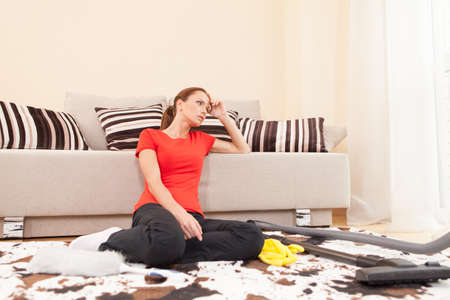Beautiful young brunette cleaning carpet. tired and exhausted girl sitting in bedroom Foto de archivo