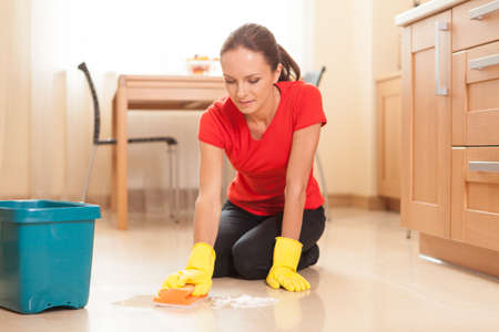 exempted female: young girl washing floor in kitchen. beautiful housewife doing cleaning and washing Stock Photo