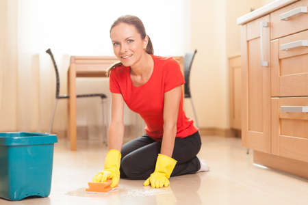 young girl washing floor in kitchen. beautiful housewife doing cleaning and smiling