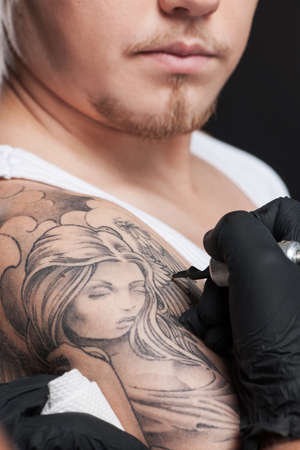 young man getting tattoo on shoulder. tattooist is drawing on hand using ink gun photo
