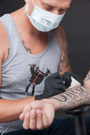 manos: tattoo professional drawing on client hand. man sitting in chair and getting tattoo