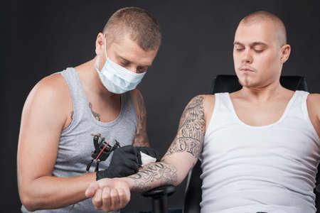 tattooing: professional tattooist doing tattoo on hand. man sitting in chair watching tattooer