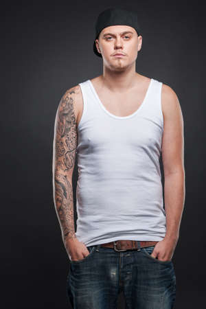 man standing with tattoo on hand and looking. young cool guy holding hands in pockets photo