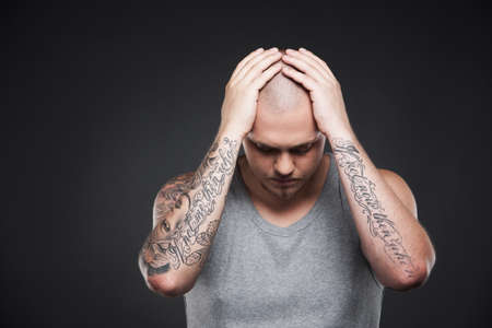 arm tattoo: young tattooed man holding head. attractive tattooed guy standing on black