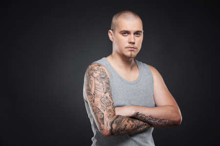 tattooed: handsome young guy standing and looking. tattooed attractive man on black background  Stock Photo