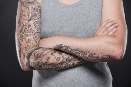 folded tattooed hands of young guy. young male standing on black background photo