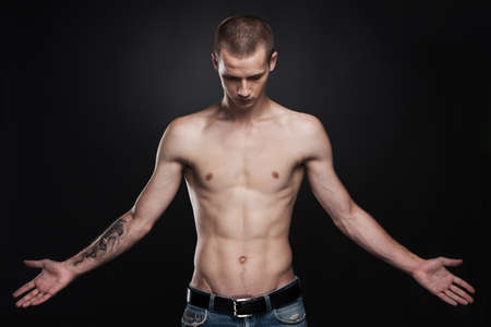 attractive young man standing with tattoo. handsome male wearing jeans on black photo