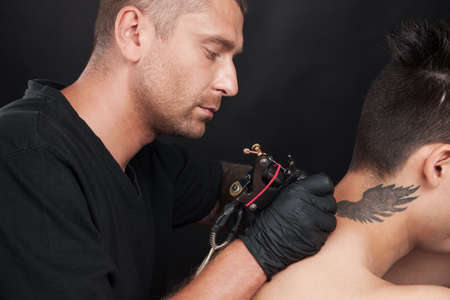 punk hair: professional tattooist drawing on man neck. tattooer drawing picture of wings on back