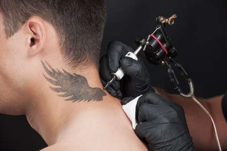 professional tattooist drawing beautiful wings. tattoo on neck using ink gun photo