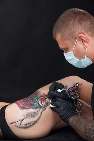 professional tattooist drawing rose on leg. red rose tattoo on girl leg
