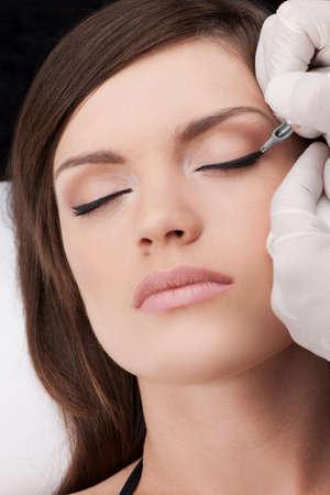 beautiful young girl getting tattoo. professional making eyes tattoo of woman Standard-Bild