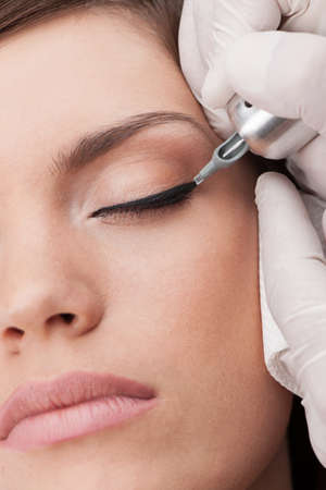 brows: professional tattooist making permanent make-up. beautiful young woman getting tattoo