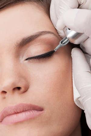 makeup model: tatuatore professionista rendendo trucco permanente. bellissima giovane donna ottenere tatuaggio