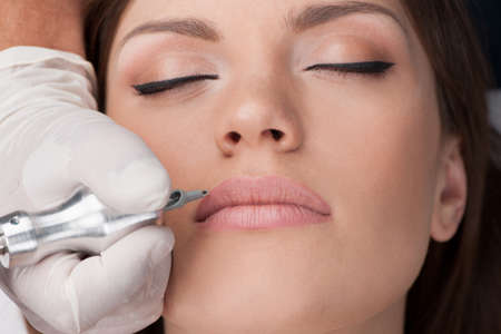 mujer maquillandose: hermosa joven que consigue el tatuaje. tatuador profesional haciendo maquillaje permanente