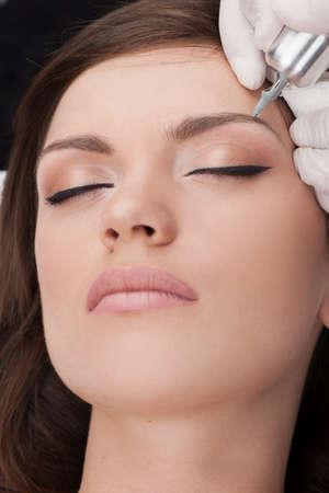 schöne junge Dame, die Tätowierung. professionelle Tätowierer machen Augenbrauen-Make up