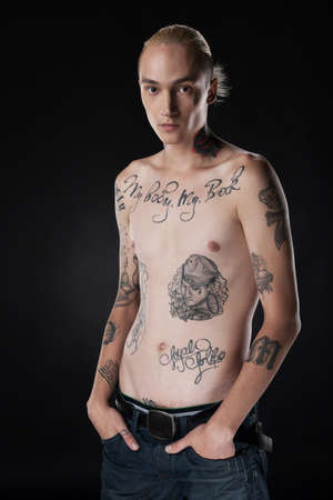 young man with tattoo on chest. adult male standing with hands in pockets photo