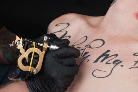 adult  body writing: professional tattooist making chest tattoo. young guy getting letters tattoo Stock Photo