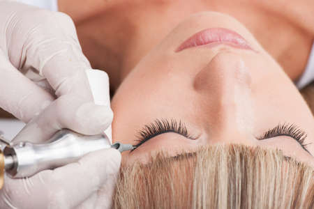 look make: professional tattooist making permanent make up. beautiful girl laying closed eyes