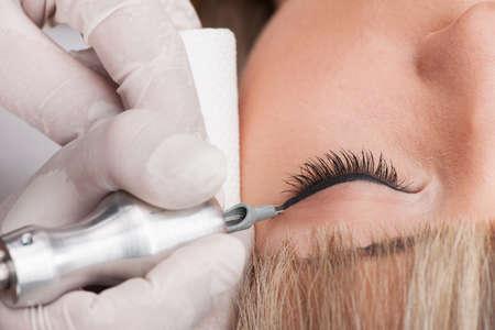 professionelle Tätowierer macht Permanent Make-up. attraktive Dame, die Gesichtspflege und Tattoo