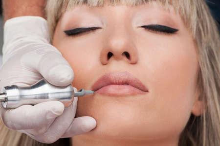 makeup model: tatuatore professionista rendendo trucco permanente. bella donna che ottiene tatuaggio sul viso