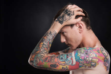 men body: man with tattoo holding head with hands. young male with colorful tattoo on black