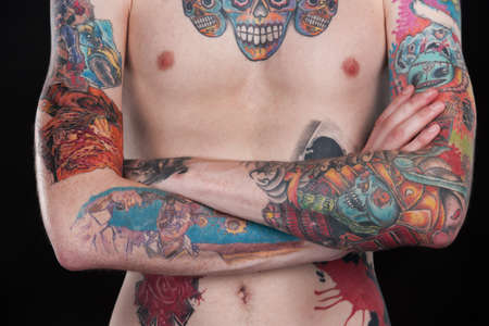 traditional tattoo: colorful tattoo chest of young man. tattoo covered body with folded hands