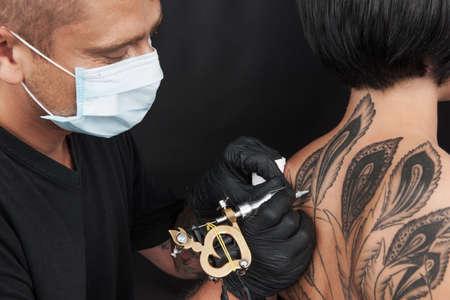 artistas: tatuador profesional haciendo la espalda tatuajes. Chica joven hermosa que recibe el tatuaje Foto de archivo