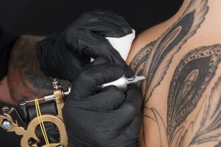 mooie jonge dame ontvangt tatoeage. professionele tatoeëerder het maken van back tattoo