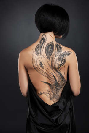 beautiful young lady with back tattoo. dark hair girl with tattoo on black background