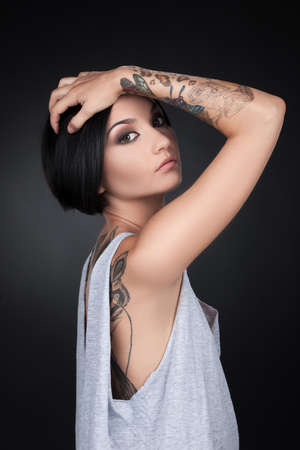 beautiful young girl with tattoo hands. attractive female holding head and looking photo