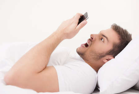 dismayed: young handsome man holding telephone. dismayed male guy waking late