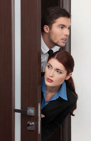 beautiful young couple entering room. handsome and pretty woman opens door photo