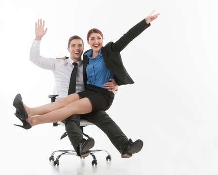 miniskirt: young attractive couple sitting on chair. two beautiful colleagues playing and laughing Stock Photo