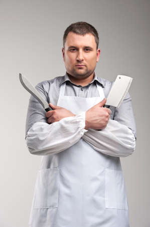 pointed arm: young butcher standing and looking serious. man holding two butcher knives