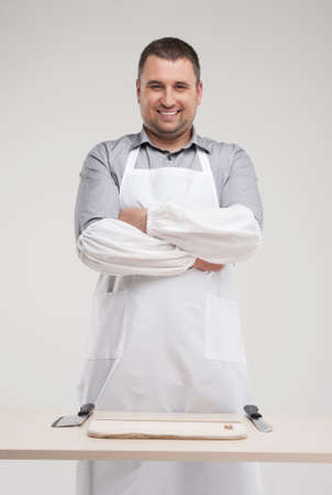 smiling butcher standing behind table. professional butcher and two knives on table Stock Photo