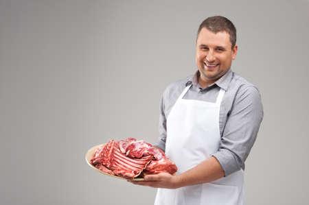 carne cruda: carnicero profesional sonriendo y sosteniendo la carne cruda. joven chef que demuestra la carne roja