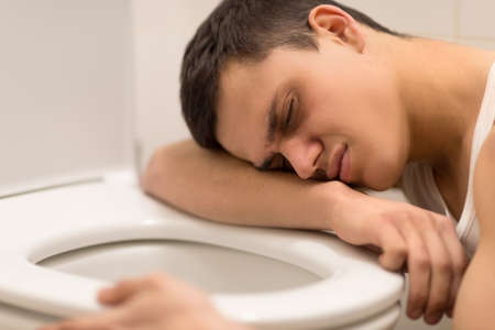 young man lying on toilet seat. drug addict kneeling over toilet seat