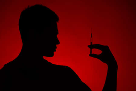 young man holding needle in hands. drug addict standing on red background