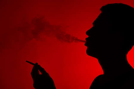 young man smoking cigarette on red. smoker exhaling smoke and holding cigarette