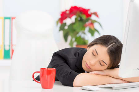 break from work: beautiful brunette sleeping at work after break. closeup of girl resting on white background