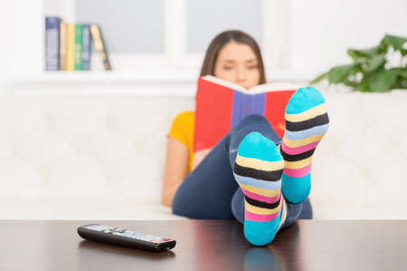 young girl sitting on couch and reading. beautiful brunette putting feet on table photo