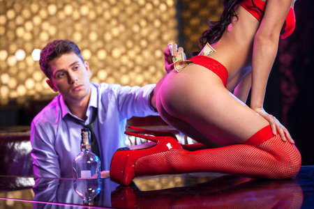 Young man putting dollars in striptease dancer panties.