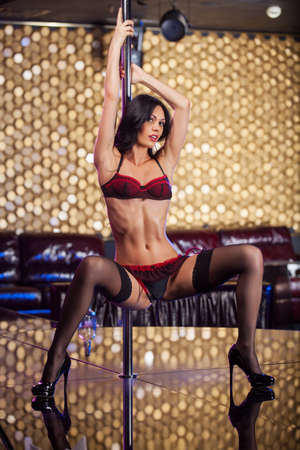 Sexy pole dancer posing on camera. Dancing in luxury and fashionable strip club  photo