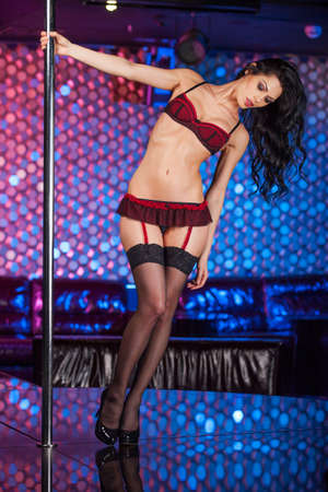 Sexy show of Beautiful pole dancer. Holding and turning around pole in strip club  photo