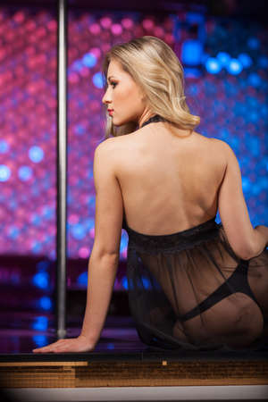 Back view of sexy blond striptease dancer. Sitting on stage in black see through dress photo