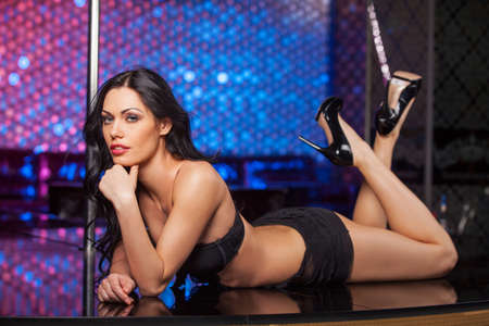 Sexy brunet dancer laying on the stage. Fashion posing in strip club  photo